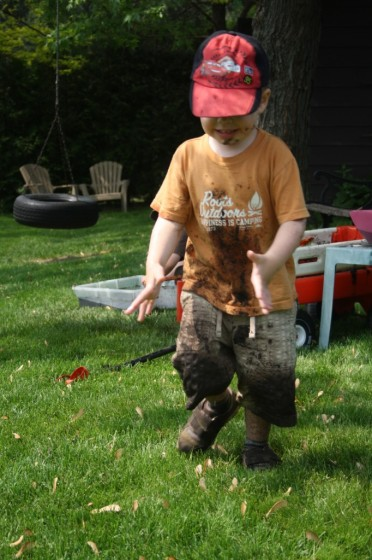 toddler with muddy shirt and shorts