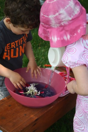 Preschooler pouring coloured water into large bowl during a science experiment