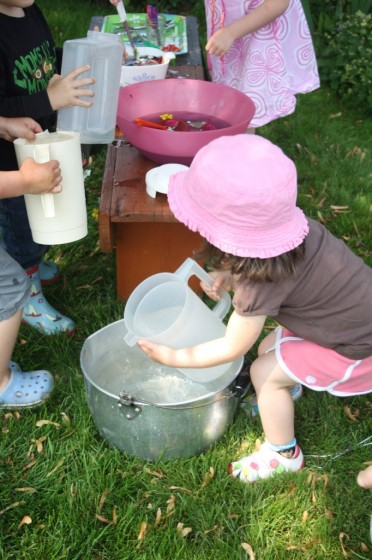Toddlers and Preschoolers filling pitchers of water in the garden for science learning