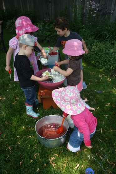 Preschoolers and toddlers cutting flowers into bowls of water during science play