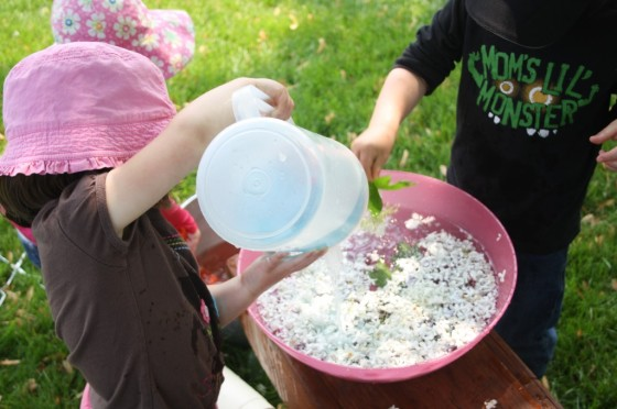 "Toddlers pouring pitchers of water into a bowl of ""garden soup"" science activity"