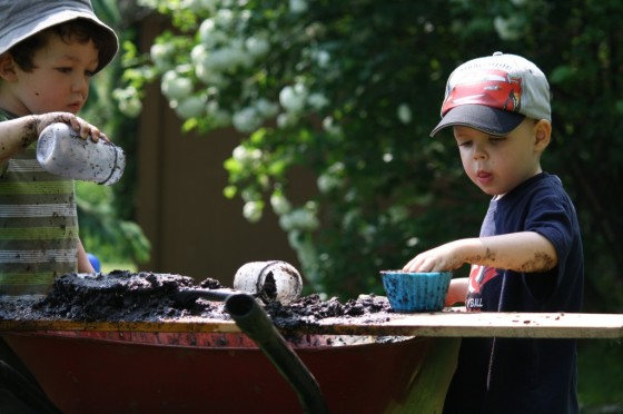 Kids playing in wheelbarrow of mud