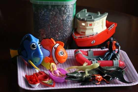 ocean toys and small stones on plastic tray