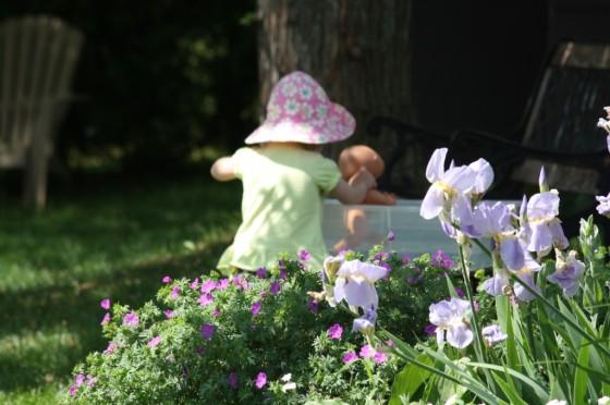 toddler in yard at water sensory bin