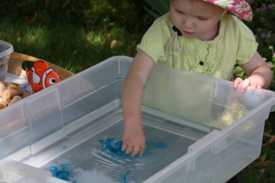 toddler playing in ocean sensory bin