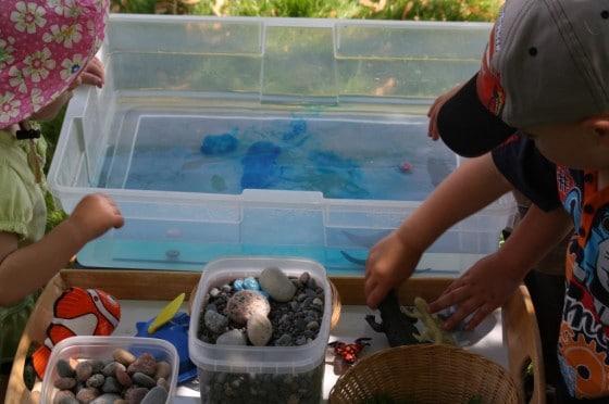 toddlers putting items into ocean sensory bin