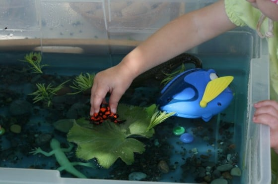 toddler putting toy frog on lily pad in sensory bin