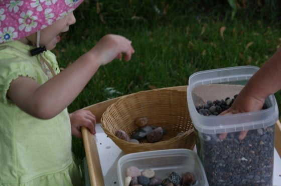 toddler putting rocks in sensory bin