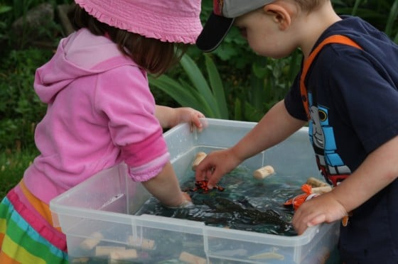 preschool girl and boy at ocean sensory bin