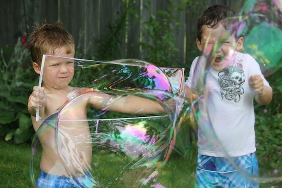 Boys blowing giant homemade bubbles in the yard