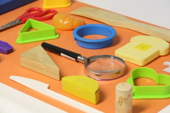toys and kitchen items laid out on paper for a matching game