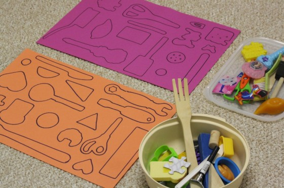 outlines of kitchen tools and toys on construction paper