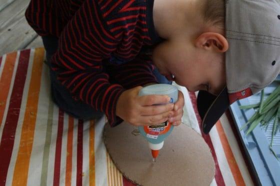 preschool boy squeezing bottle of glue