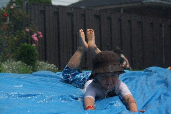preschool boy sliding head first on homemade water slide