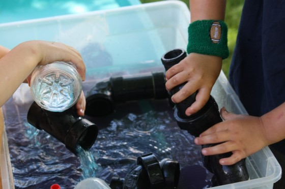 science activities: kids playing with water play activity bin