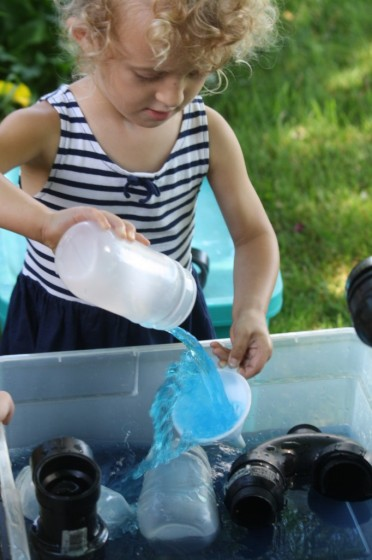 preschooler pouring water through funnels during science activities