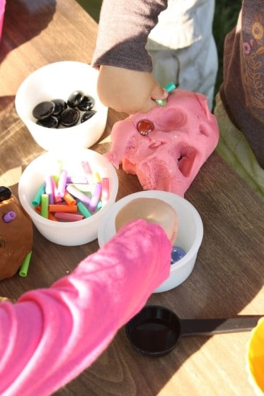 kids pressing beads into pink play dough