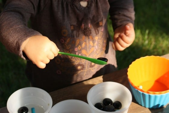 toddler scooping black beads with small green spoon