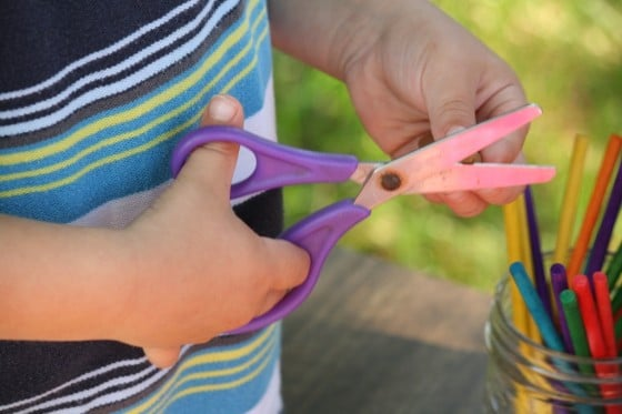 preschooler cutting play dough with scissors