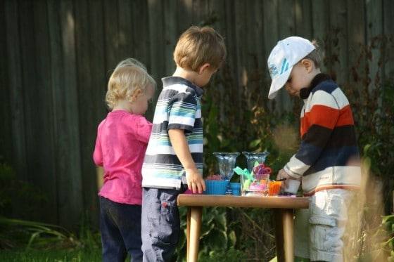 toddler and preschoolers gathered around play dough table in backyard