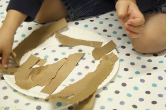 toddlers gluing paper strips to paper plate