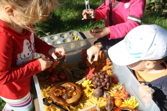 preschoolers and toddler playing with fall sensory bin