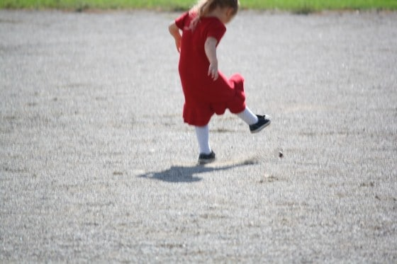 preschool girl in red dress kicking stone
