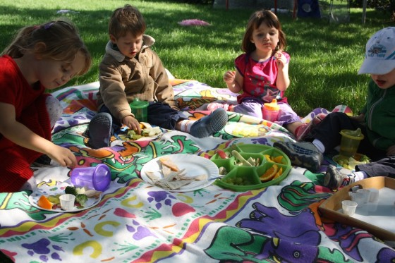 toddler and preschoolers having lunch on blanket under tree
