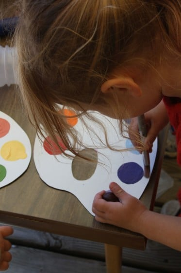 preschooler dipping paintbrush in purple paint on pretend paint palette