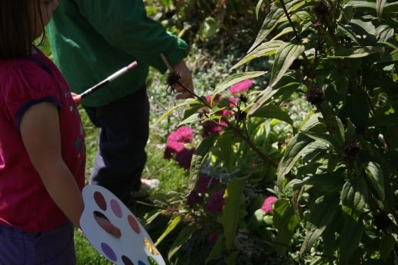 toddlers painting the flowers in the garden with pretend paint palettes