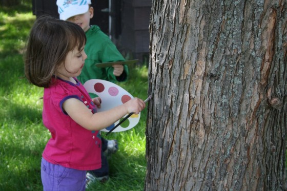 toddlers using pretend paint palette to paint the trees