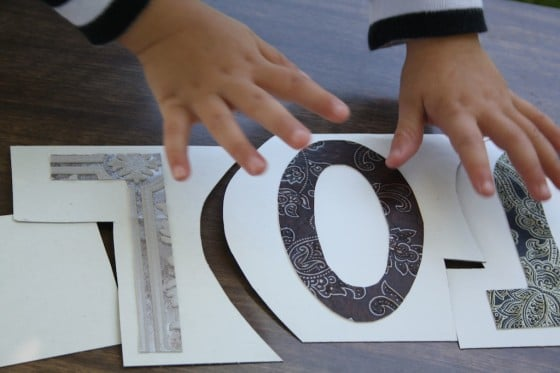 preschoolers hands and homemade name puzzle