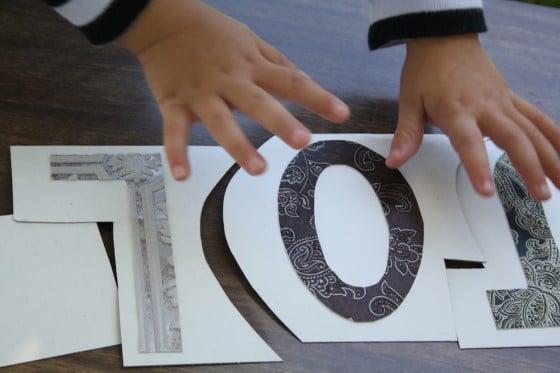 preschooler putting together cardboard name puzzle