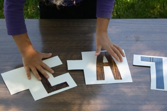 Child putting together pieces of homemade name puzzle