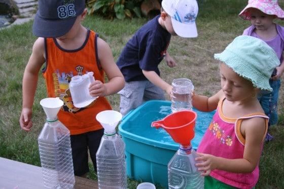preschoolers filling plastic juice jugs with water
