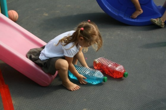 4 year old girl on slide with blue and red bottle babies