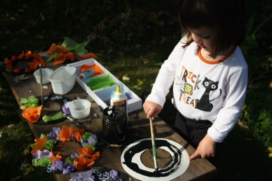 child painting paper plate wreath for halloween