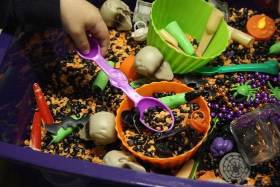 scooping beans in the halloween bin