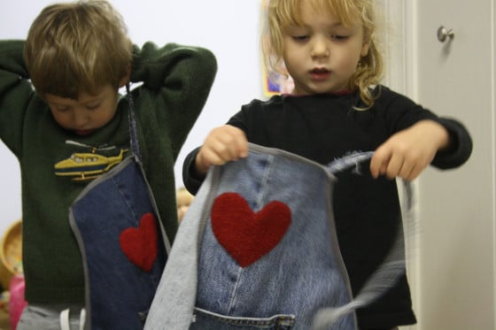 kids putting on denim craft aprons
