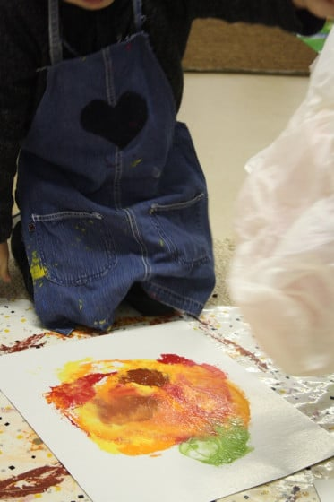 child lifting bag off smoosh painted pumpkin