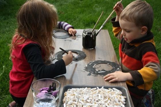 preschoolers painting black paper plate wreaths for Halloween