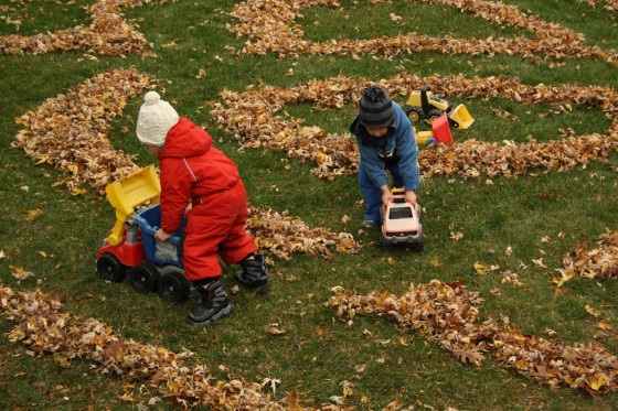 kids pushing toy trucks through roads made in leaves