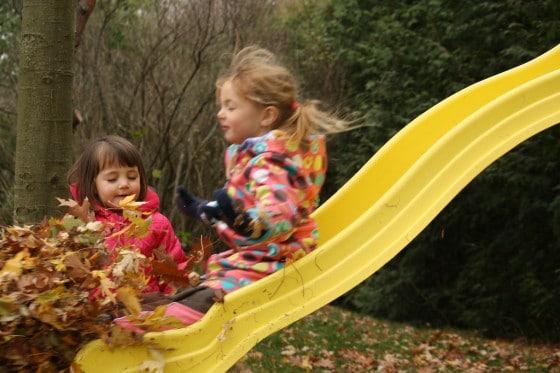 preschool girl sliding down slide into pile of leaves