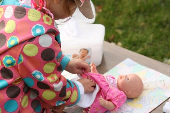close up of preschooler diapering a doll