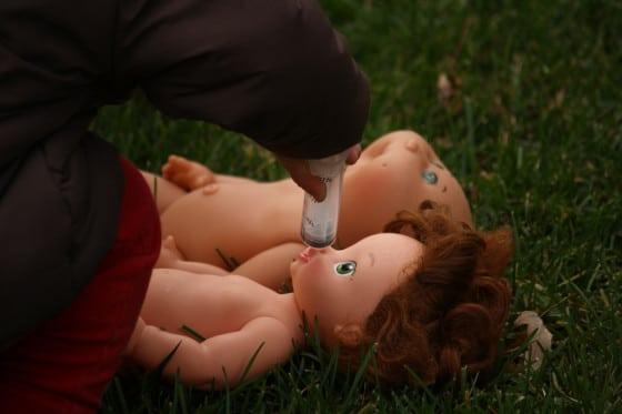 preschooler giving doll pretend medicine