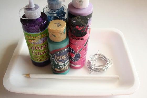 paint, styrofoam tray, glitter glue, white pencil crayon, string