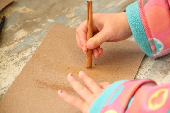 toddler rubbing cinnamon stick on sandpaper