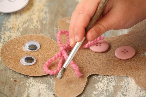 child decorating sandpaper gingerbread man