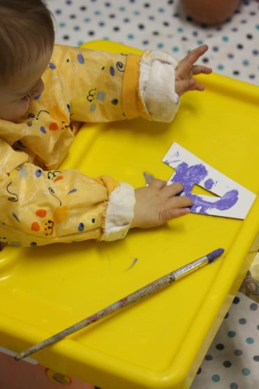 baby finger painting on cardboard letter A