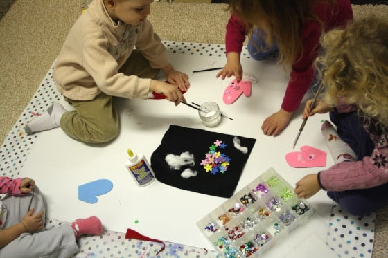 toddlers and preschoolers gluing craft gems to felt mittens